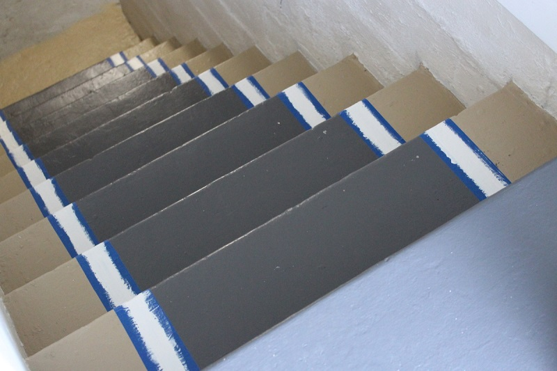 Painters tape on stairs showing how to add painted edge to stair runner