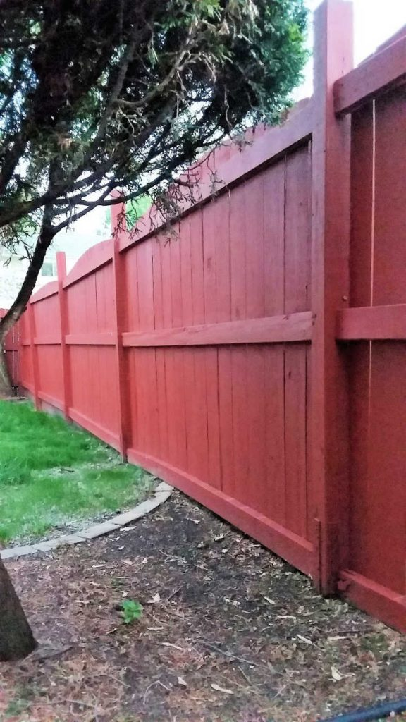 Straight, Tall Navajo Red Stained Wood Fence