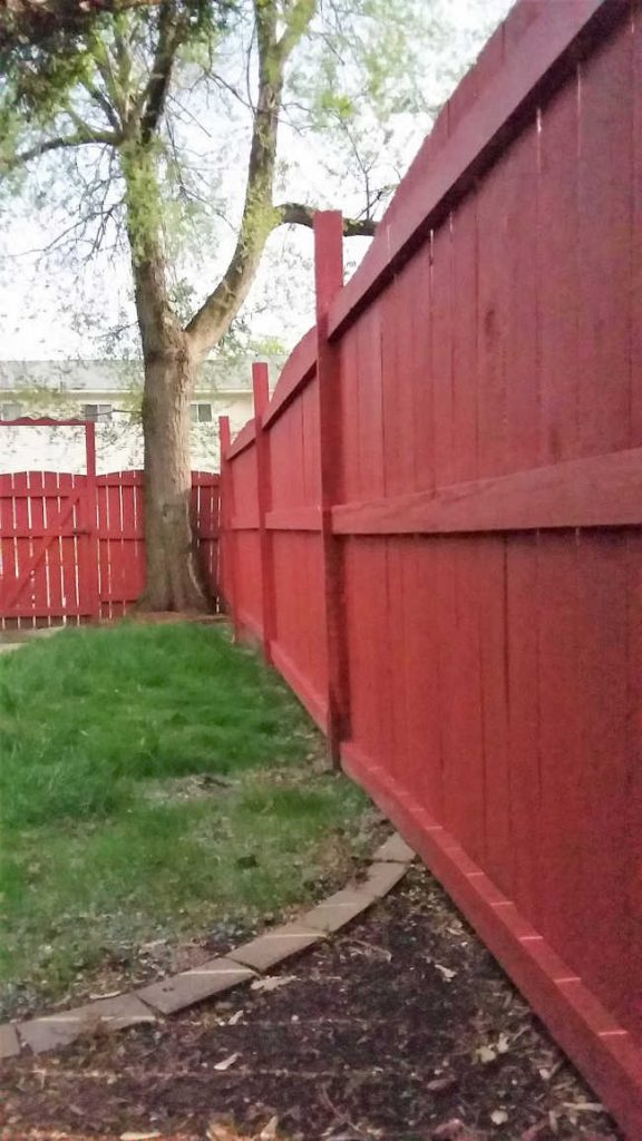 red, leaning fence repaired with post buddy