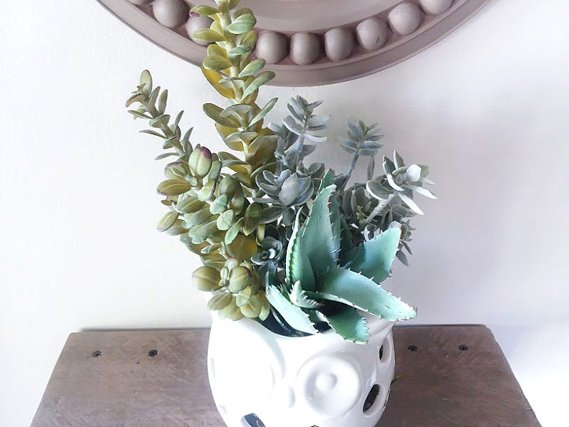 Variety of faux stems in white planter