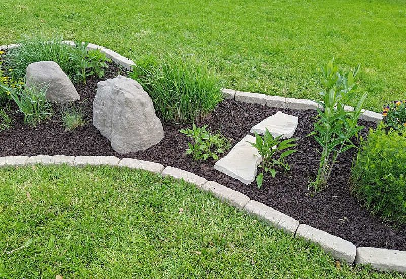 Garden bed with tumbled edgers, fake rock accents, brown rubber mulch