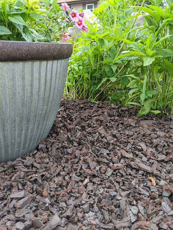 Artificial outdoor landscaping with brown rubber mulch