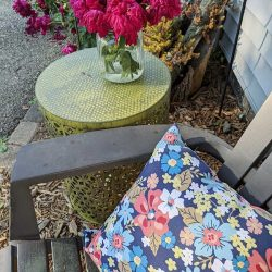 Green painted metal patio table, with chair and pillow and flowers