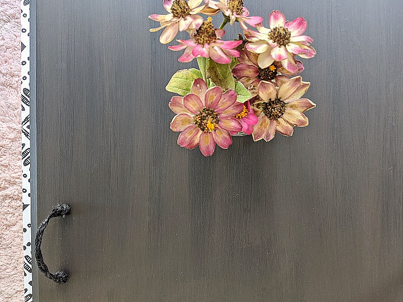 faux-black-brown painted table top with a floral arrangement