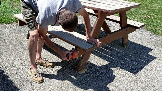 man sanding picnic table