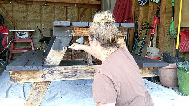 woman rolling solid stain on picnic table