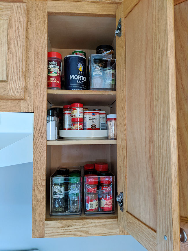 Organized spice cabinet with pull-out bin storage